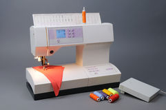 Sewing Machine with Threads and fabric. On grey background Stock Photos