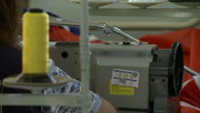 Sewing machine view with changing focus. Sewing manufacture view of a running sewing machine and big spool of thread with a changing focus stock video footage