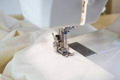 Sewing machine with white fabric under the needle and the presser foot, close up. Selected focus, narrow depth of field stock images