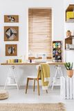 Sewing machine on a wooden desk by the window in a scandi crafts room interior with white walls and yarn. Real photo. Sewing machine on a wooden desk by the stock image