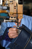 Sewing machines. The worker sewing a handbag by sewing machines royalty free stock image