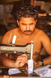 Sewing man in Nepal. Damak, Nepal - circa May 2012: Half-naked man with moustache sits and sews by sewing maschine at Nepali refugee camp in Damak, Nepal stock photography