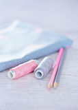 Sewing materials, pencils, fabric on a blue and pink color Royalty Free Stock Photo