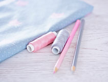 Sewing materials, pencils, fabric on a blue and pink color Royalty Free Stock Image