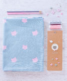 Sewing materials, pencils, note, fabric on blue and pink color Royalty Free Stock Images