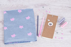 Sewing materials, pencils, notes, fabric on a blue and pink color Stock Photos