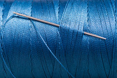 Sewing needle in blue thread bobbin Royalty Free Stock Image