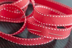 Sewing needle in a red ribbon. Closeup, industrial concept Stock Photos
