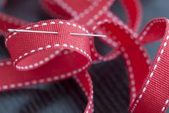 Sewing needle in a red ribbon. Closeup, industrial concept Stock Photo