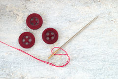 Sewing needle, red thread and a button top view Royalty Free Stock Image