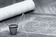 Sewing needle and thimble Stock Photos
