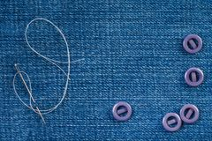 Sewing needle with a white thread and lilac buttons on a denim fabric with copy space stock photo