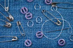 Sewing needle with a white thread, lilac and transparent buttons and pins on a denim fabric royalty free stock photography