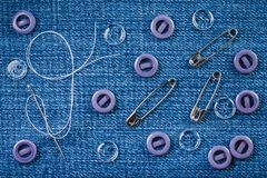 Sewing needle with a white thread, lilac and transparent buttons and three pins on a denim fabric stock photography