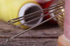 Sewing needles close-up on a background of spools of thread. Stock Photo