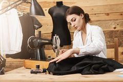 Sewing is not just work, it is flair. Creative designer working with sewing machine under her new garment line, being. Focused and putting efforts to make it royalty free stock photography