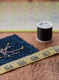 Sewing notions on a rustic wood surface. Sewing notions such as fabric, pins, tape measurer, spool of thread and quilting grid sit on top of a rustic wood Stock Image