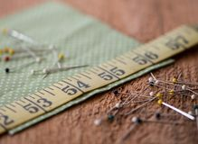 Sewing notions on a rustic wood surface. Sewing notions such as fabric, pins, tape measurer and quilting grid sit on top of a rustic wood surface Stock Photos