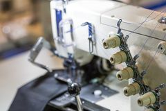 Sewing or overlock machine closeup, cloth industry. Sewing or overlock machine closeup, nobody, cloth industry. Factory production, sew manufacturing Stock Photos