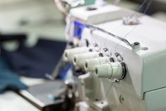 Sewing or overlock machine closeup, cloth industry. Sewing or overlock machine closeup, nobody, cloth industry. Factory production, sew manufacturing Stock Images