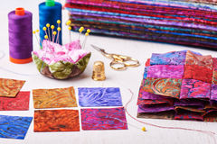 Sewing patchwork blocks to colorful batik quilt royalty free stock photos