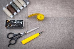 Sewing pattern composition with scissors, spools of thread, pins, measuring tape royalty free stock photo