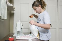 Sewing a pillow 1. Young girl standing at a sewing machine stuffing and sewing a pillow Royalty Free Stock Image
