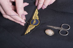 Sewing pilots wings onto uniform Stock Photography
