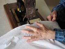 Sewing process. Foot of old vintage sewing machine and hand. Selective focus royalty free stock photos