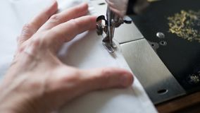 Sewing process. Foot of old vintage sewing machine and hands of elderly woman. Selective focus.  royalty free stock images