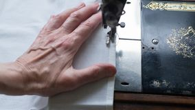 Sewing process. Foot of old vintage sewing machine and hands of elderly woman. Selective focus.  stock photo