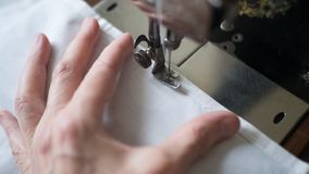 Sewing process. Foot of old vintage sewing machine and hands of elderly woman. Selective focus.  royalty free stock image