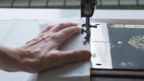 Sewing process. Foot of old vintage sewing machine and hands of elderly woman. Selective focus.  stock image