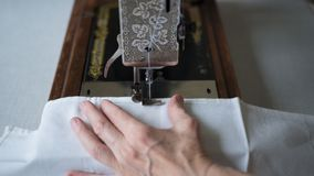 Sewing process. Foot of old vintage sewing machine and hands of elderly woman. Selective focus.  royalty free stock photography