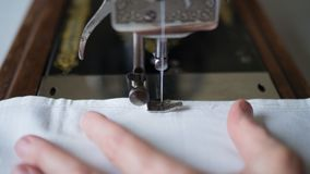 Sewing process. Foot of old vintage sewing machine and hands of elderly woman. Selective focus.  stock images