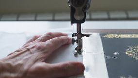 Sewing process. Foot of old vintage sewing machine and hands of elderly woman. Selective focus.  royalty free stock photo