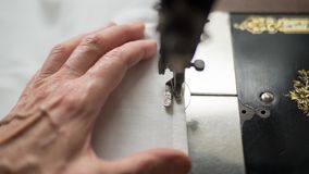 Sewing process. Foot of old vintage sewing machine and hands of elderly woman. Selective focus. Front view royalty free stock photography