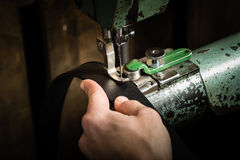 Sewing process of the leather belt. Man's hands behind sewing. Leather workshop stock photo