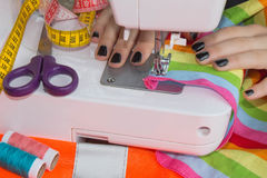 Sewing Process , the sewing machine sew women`s hands. sewing machine and female scissors Stock Photo