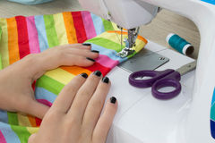Sewing Process , the sewing machine sew women`s hands. sewing machine and female scissors Royalty Free Stock Photo