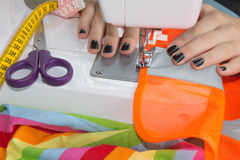 Sewing Process , the sewing machine sew women`s hands sewing machine. sewing machine and female scissors Royalty Free Stock Photos