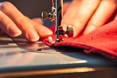 Sewing Process. Women's hands behind her sewing royalty free stock photo
