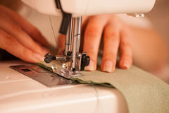 Sewing Process - Women taylor's  hands behind her sewing machine Stock Image