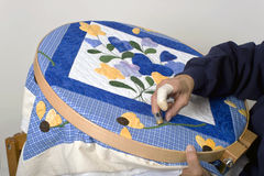 Sewing on quilt hoop. A quilter works on a colorful quilt on a quilt hoop Stock Image