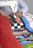Sewing a quilt. A quilter sews pieces of fabric into a colorful quilt Royalty Free Stock Photography