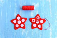 Sewing red Christmas star diy. How to sew on a white felt balls to a red felt stars. Decorative stitch. Christmas diy. Christmas diy idea for kids and beginners royalty free stock photography