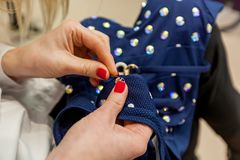 Sewing on rhinestones. Girl designer hands with a red manicure sew rhinestones to the blue swimsuit royalty free stock photography