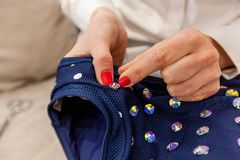 Sewing on rhinestones. Girl designer hands with a red manicure sew rhinestones to the blue swimsuit stock images