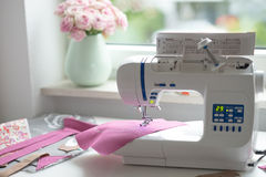 Sewing room with sewing machine, fabric, flowers and wom Royalty Free Stock Image