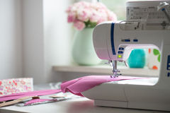 Sewing room with sewing machine, fabric, flowers and wom. View of sewing room with sewing machine, fabric, flowers and woman Stock Photo